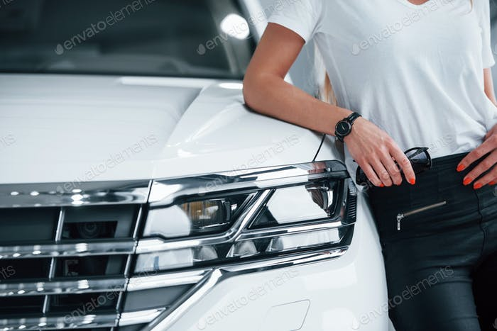 Man leaning on vehicle. Particle view of modern luxury white car parked indoors at daytime