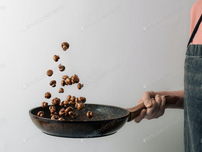 Flying champignons over skillet in hand