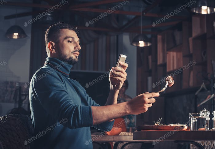 man photographing food