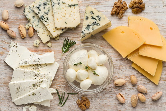 Assortment of cheese with nuts on wood