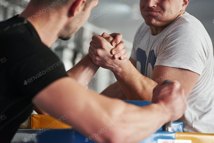 Close up view. Arm wrestling challenge between two men. Match on a special table