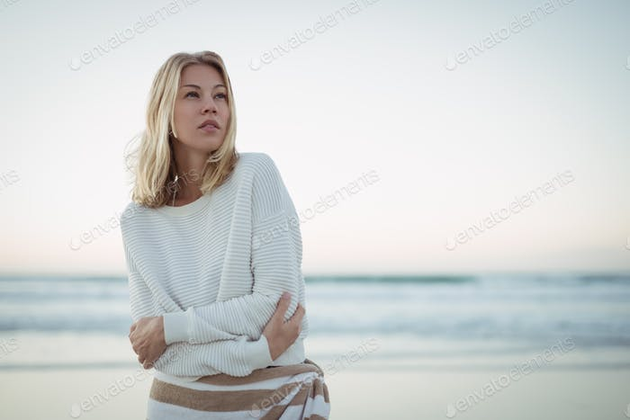 Thoughtful woman looking up at beach