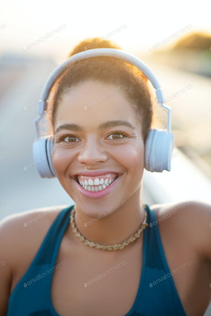 Dark-eyed woman showing toothy smile after running