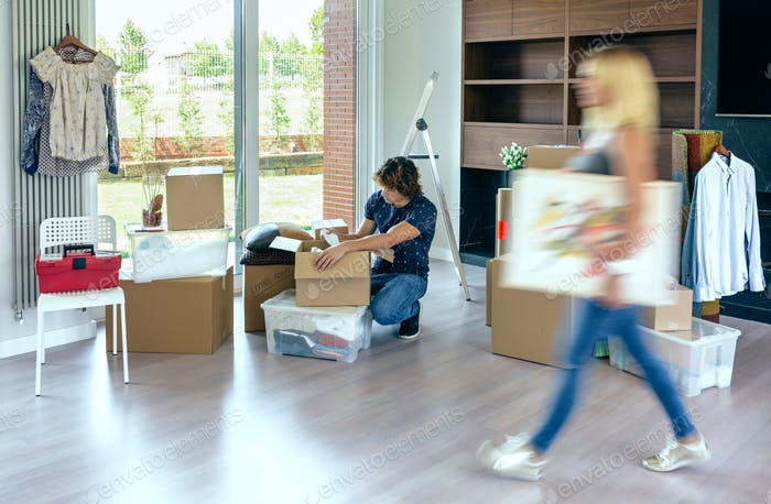 Woman carrying painting while husband unpacks