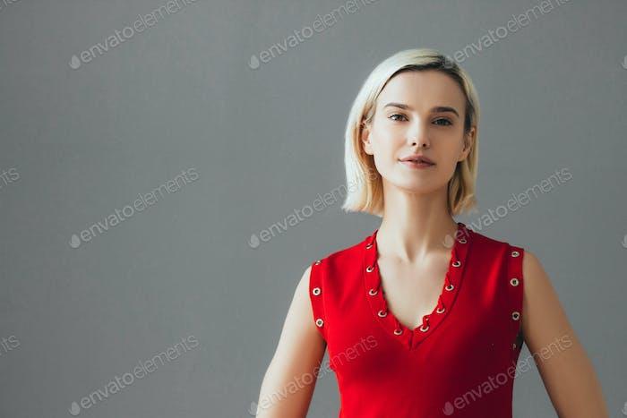 Nice woman in red dress blonde short hair. Fashion female portrait cute nice girl