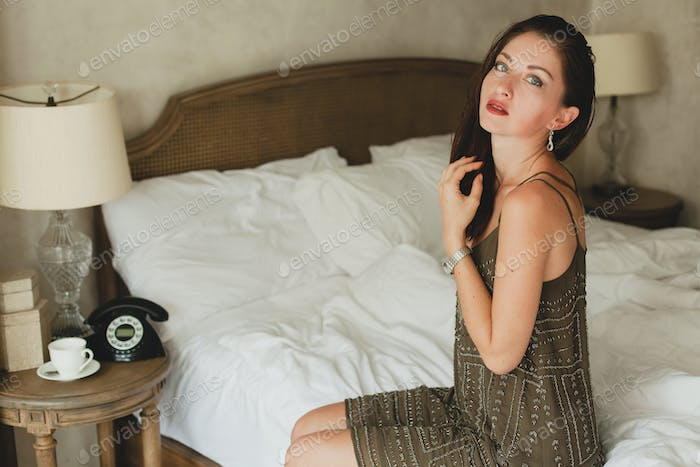 young beautiful woman sitting on bed in hotel room