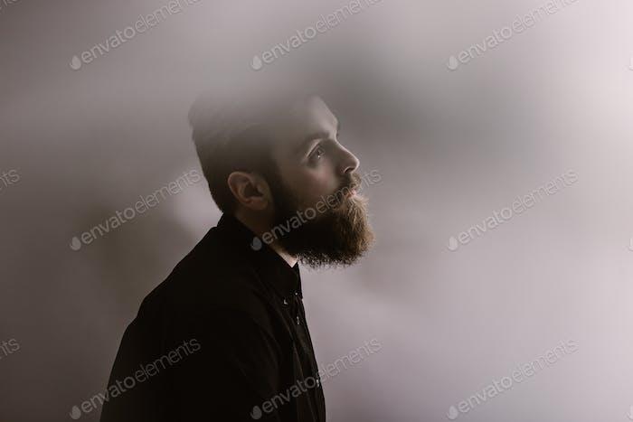 Sepia Fotoporträt eines stilvollen Mannes im Profil mit einem Bart im schwarzen Hemd im Nebel gekleidet