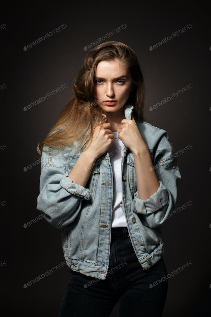 Gorgeous brunette girl with long flowing hair dressed in jeans jacket and jeans poses standing on