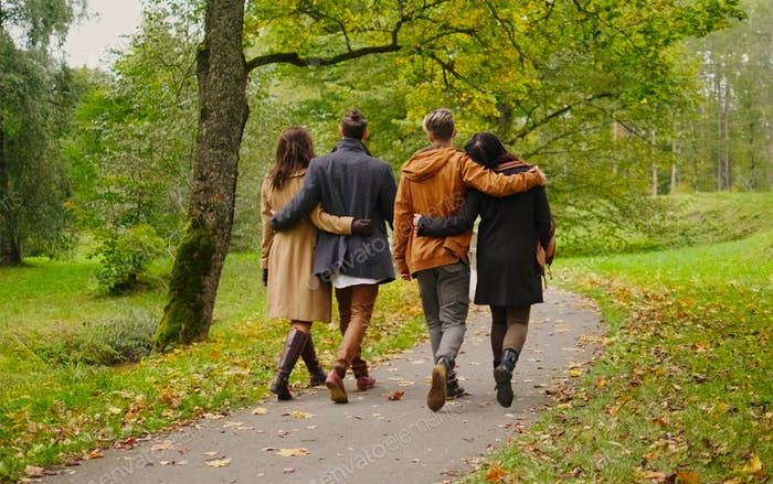 Friends walking in autumn park