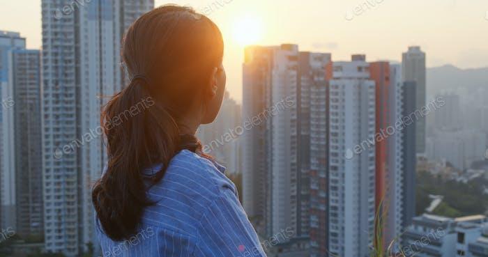 Frau schauen sich um die Stadt mit Sonnenuntergangslicht