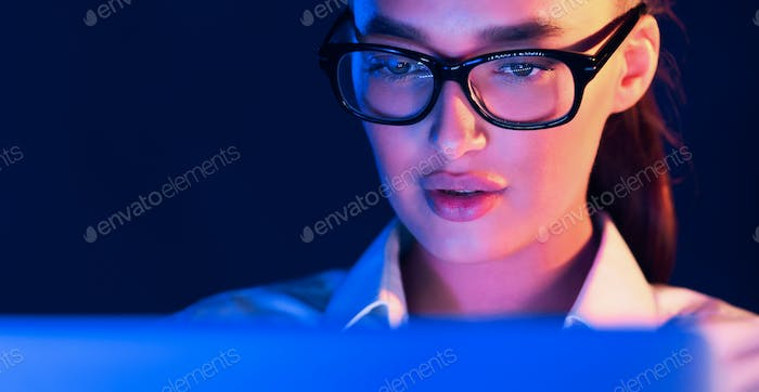 Overwork. Woman working on laptop at night