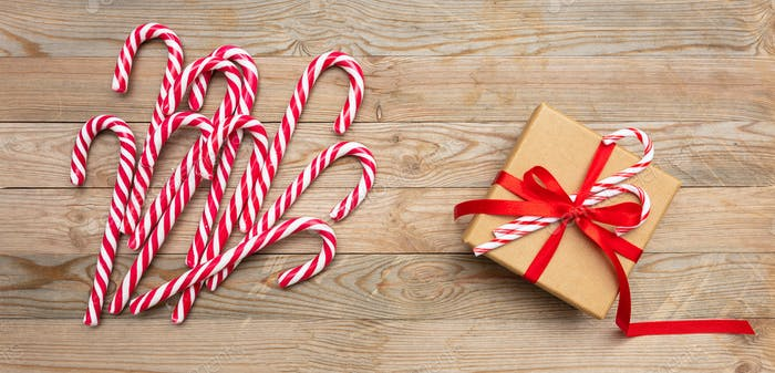 Candy canes and a gift box with red ribbon on wooden background