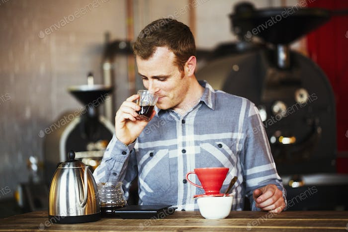 Specialist coffee shop. A man brewing coffee using a filter paper, and drinking it.