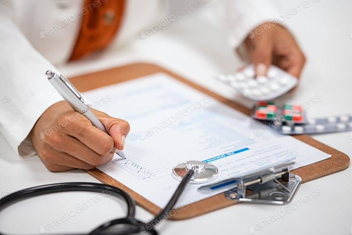 Doctor writing and checking medical prescription
