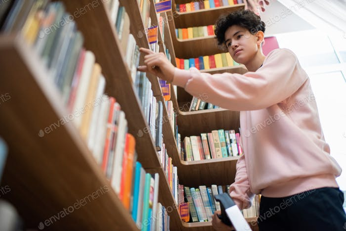 Teenage boy in casualwear taking book from shelf in college library