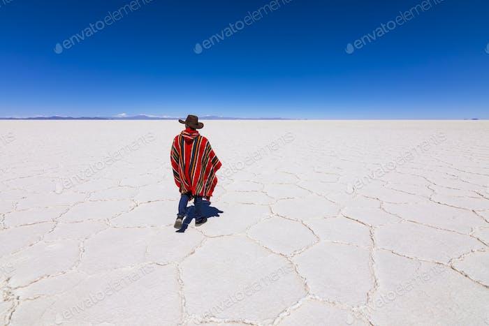 Man in poncho at Salar de Uyuni, Aitiplano, Bolivia