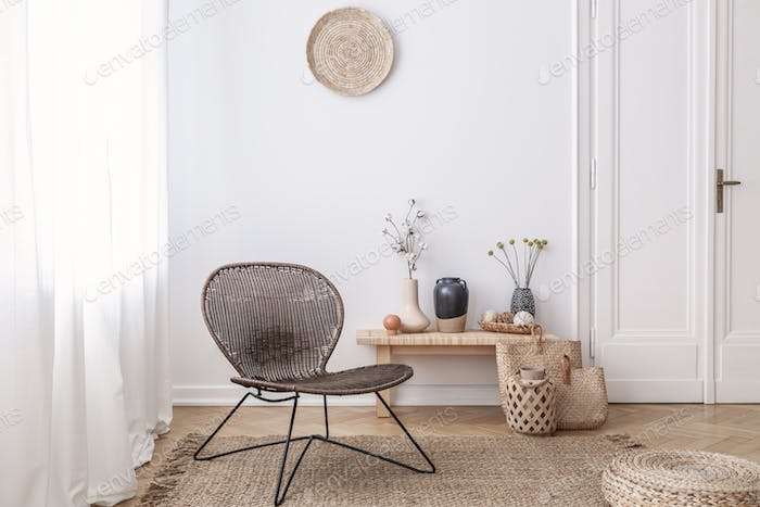 Dark, modern wicker chair in a white living room interior with a