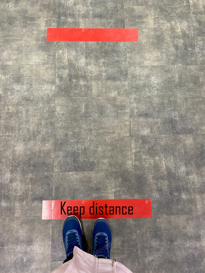 Person standing on tiled floor with a red line. Concept of keep distance, social distancing