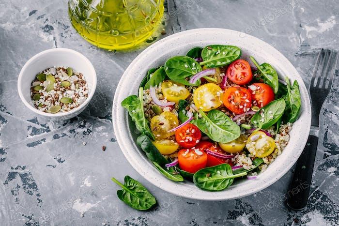 Ensalada verde saludable con espinacas, quinua, tomates amarillos y rojos, cebollas y semillas