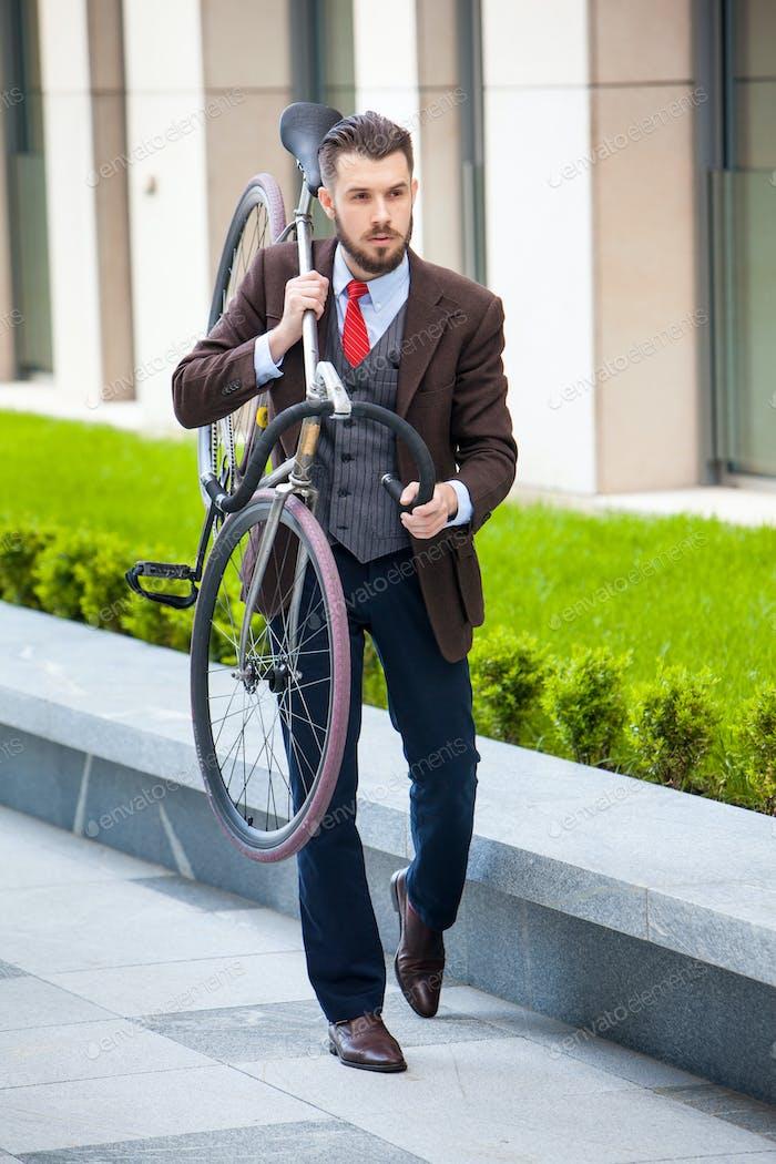 Hübscher Geschäftsmann trägt sein Fahrrad