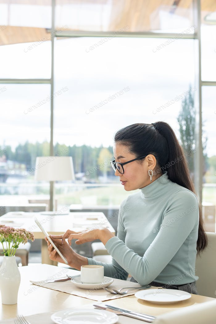 Young contemporary businesswoman of Asian ethnicity pointing at tablet display