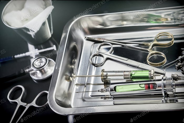 scissors and syringes on a table of operating theater of a hospital conceptual image