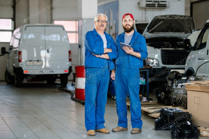 Two professional technicians of machine repair service in blue workwear