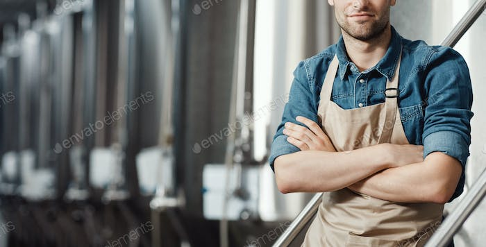 Confidence attractive guy owner or employer in apron with crossed arms at factory with big boilers
