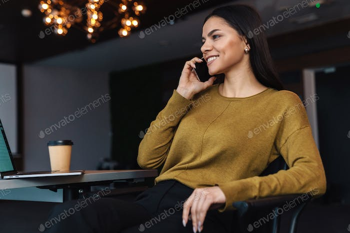 Image of young businesswoman using cellphone while working in office