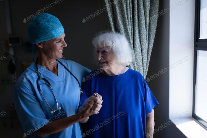 Weibliche Chirurgin und Seniorpatientin im Gespräch miteinander in der Klinik neben dem Fenster im Krankenhaus