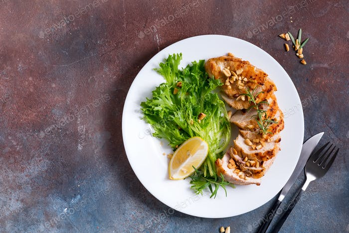 grilled chicken breast fillet with asparagus and lemon in plate and stone background