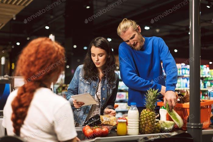 Junge Frau mit Einkaufsliste steht in der Nähe der Kasse, während