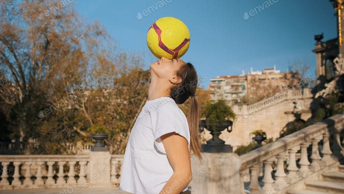 Attractive sporty girl practicing football tricks skills in city park