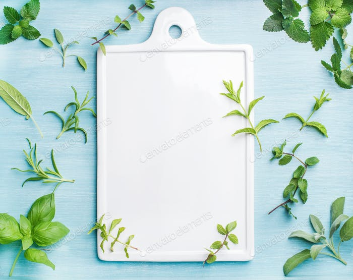 Sage, basil, rosemary, melissa and mint on blue background with copy space