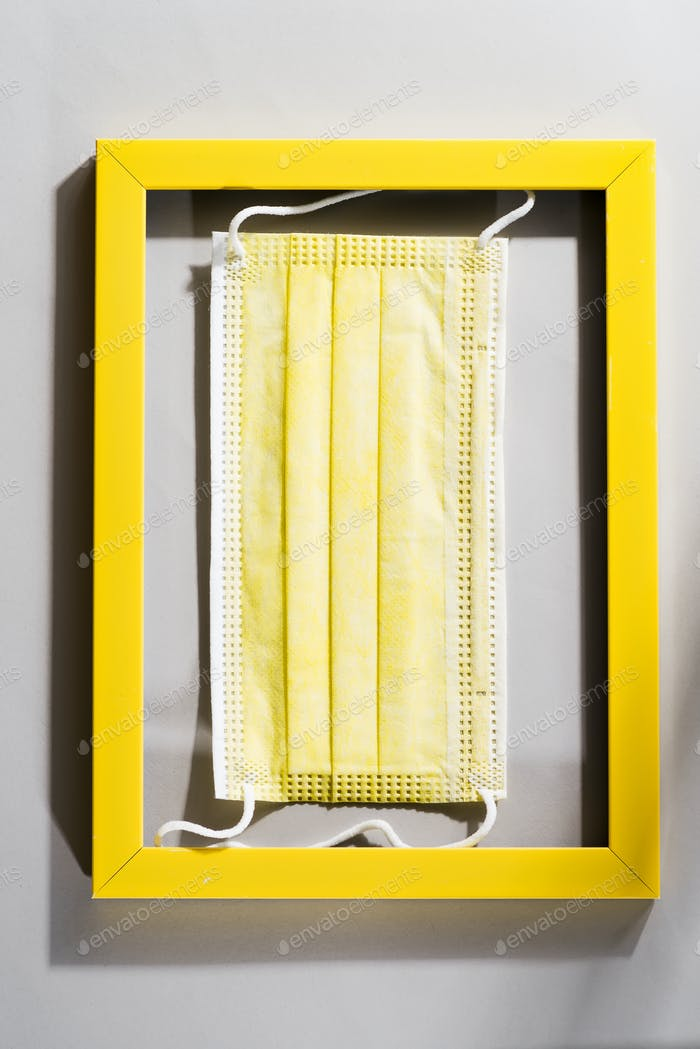 Yellow surgical face protection mask in the yellow frame on gray background. Trendy colors 2021.