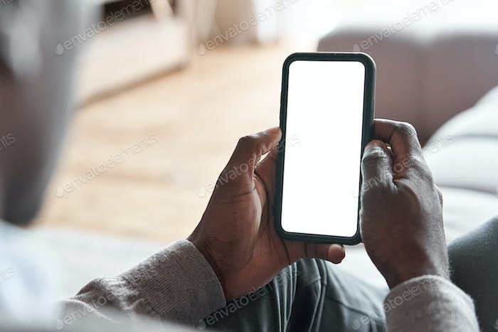 African man holding phone with mockup white screen for app ads at home.