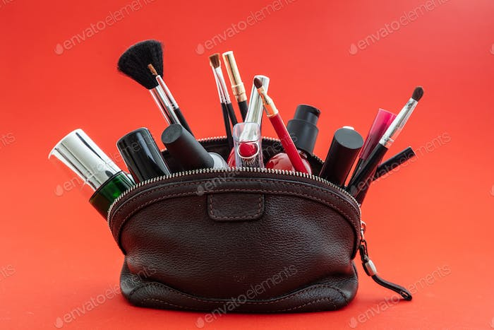 Make-up bag with cosmetics and makeup accessories against red background