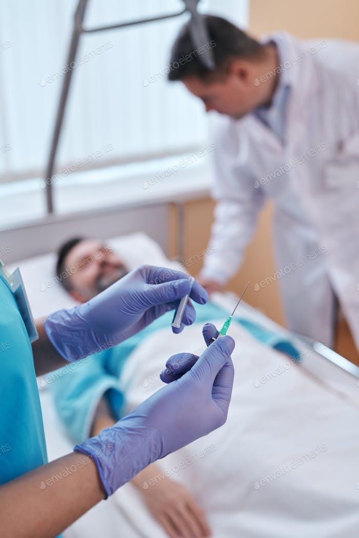 Preparing syringe needle for IV