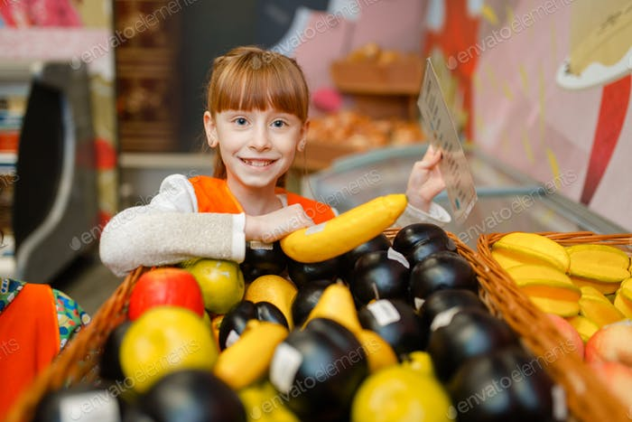 Smiling little girl in uniform playing saleswoman