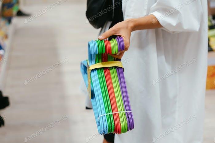 Weibliche Hand hält eine Reihe von Kleiderbügeln