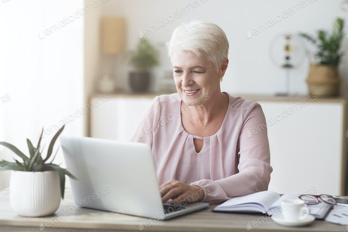 Mature business lady enjoying her job, working from home