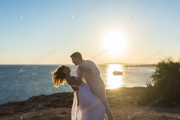 Paar umarmt und küssen einander am Strand gegen Ozean