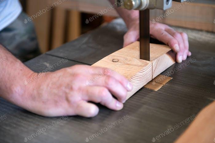 Schreiner schneidet einen Holzblock auf einer Bandsäge
