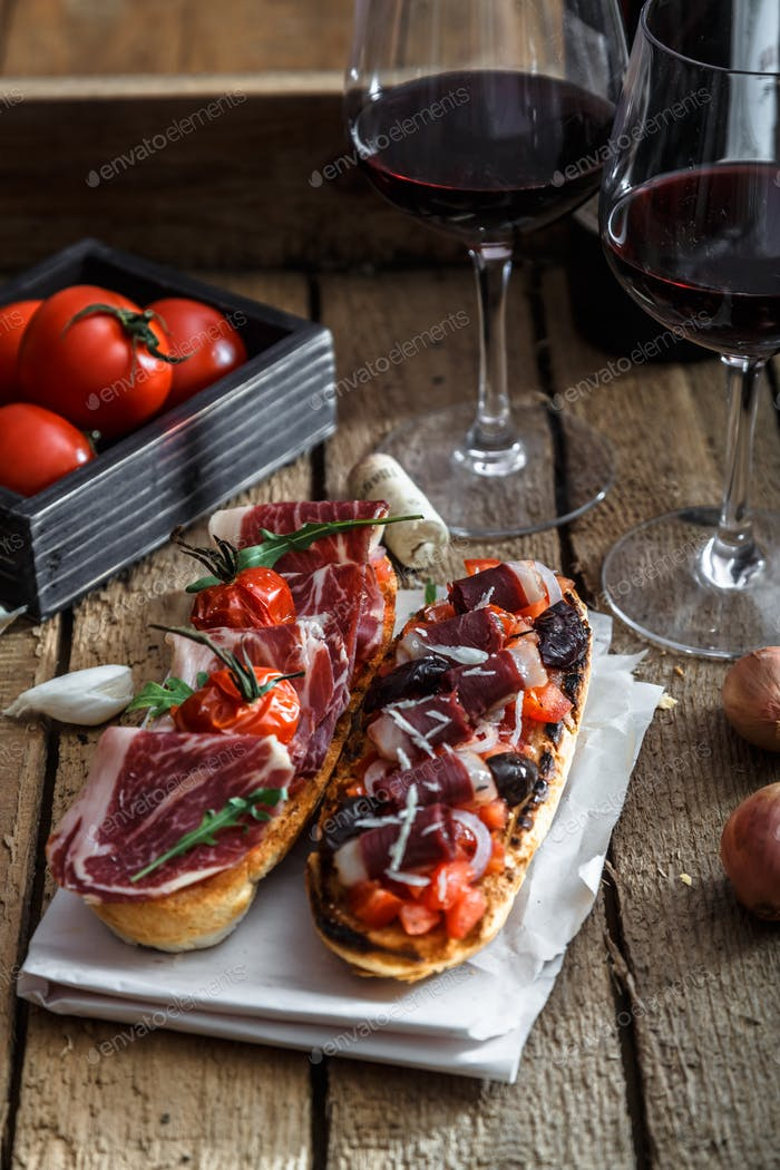 Variety of small sandwiches with jamon, tomatoes, parmesan cheese, fresh basil served with wine