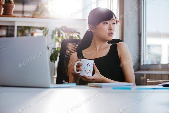 Business woman taking coffee break in office