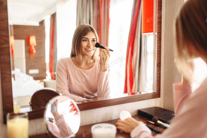 Woman with a brush in hand doing morning makeup