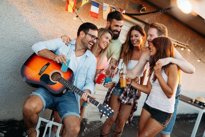 Junger Mann Gitarre spielen für Freunde und seine Freundin