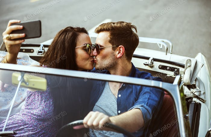 Couple Driving a Car Traveling on Road Trip Together