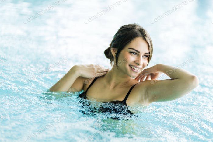 Beautiful young brunette relaxing in a swimming pool