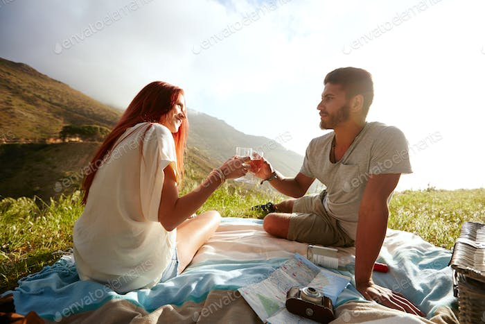 Romantic couple enjoying a day with wine, outdoors.